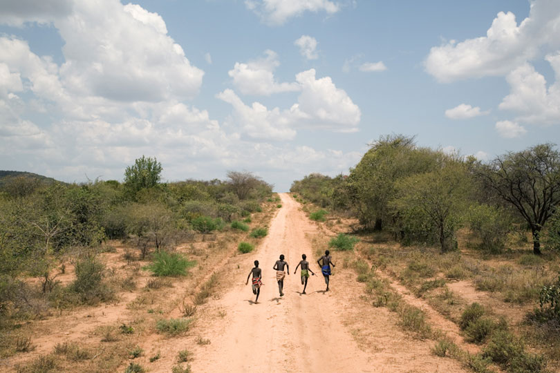 Four boys running down Dirt Road, Omo Valley, Ethiopia. © Andrew Geiger