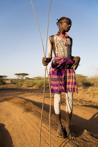 Cow Herder posing at sunset, Omo Valley, Ethiopia. © Andrew Geiger