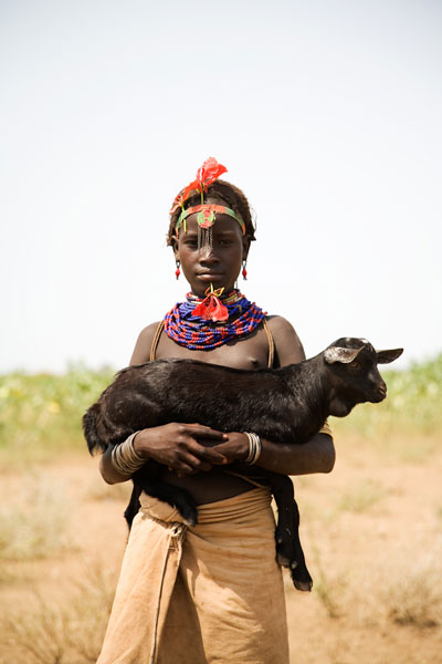 Girl Holding Goat with Baobab flower through lip, Omo Valley, Ethiopia. © Andrew Geiger